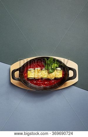 Eggplant rolls with cheese in tomato sauce. Served restaurant dish in oval cast iron dish. Fancy meal decorated with parsley. Food preparation art. Cooked aubergine in casserole dish on wooden board