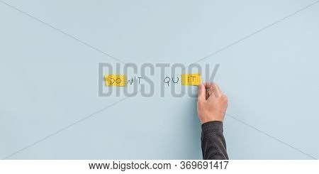 Male Hand Making A Dont Quit Sign That Also Reads Do It. Over Blue Background.