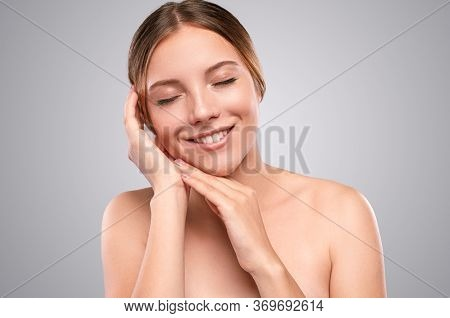 Delighted Young Woman With Closed Eyes Smiling And Touching Soft Clean Skin After Spa Procedure Agai