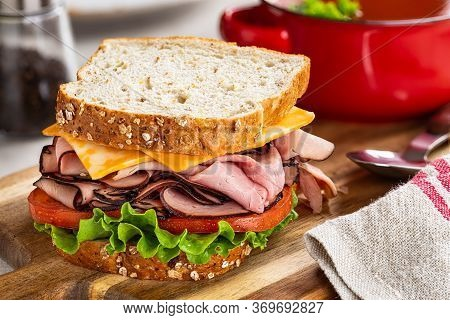 Closeup Of Ham Sandwich With Cheese, Tomato And Lettuce On Whole Grain Bread  With Bowl Of Soup In B