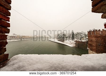 Adige River In Verona Downtown Seen From The Medieval Scaligero Bridge Of Castelvecchio In Winter Wh