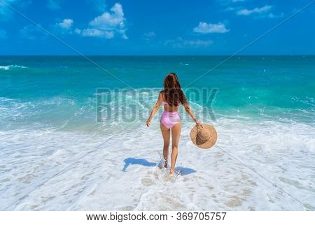 Beautiful Girl In A Swimsuit On A Sandy Beach On The Ocean. A Girl With A Straw Hat In Her Hands Is