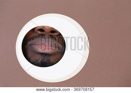 Keep Silent. Copyspace. Lips Of African-american Man Peeks Throught Circle In Brown Background. Tren