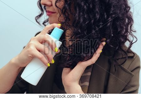 Girl Using Spray To Make Curly Hairstyle. Woman With Long Curly Hair. Female Apply Cosmetic Care Pro