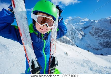 Cute Skier Boy With Ski Standing In Bright Outfit Over Mountains Close Portrait