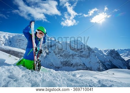 Cool Little Skier Sitting With Ski In Snow Over Sunny Mountain Panorama Copy Space