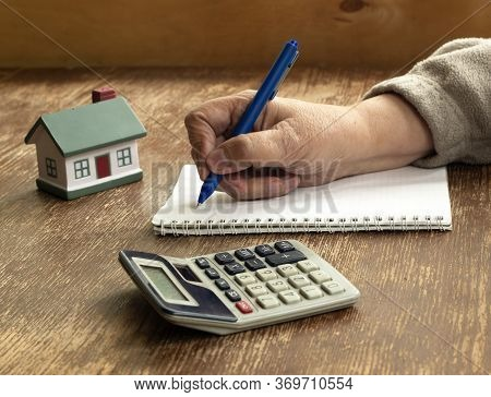 On An Old Wooden Table Is A Calculator, A Small House, A Notebook And A Pen. The Concept Of Buying,