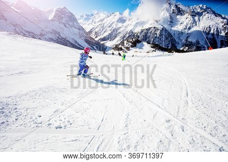 Girl In Colorful Ski Outfit Go Downhill Fast In The Mountains