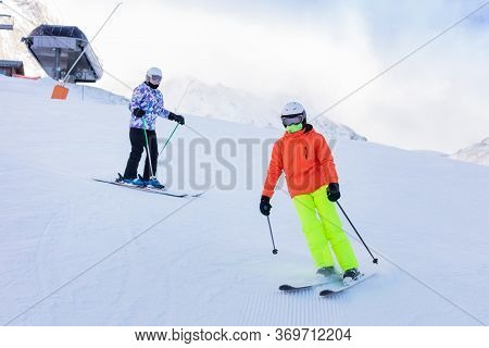 Two Girls Ski Downhill Together In Colorful Outfit On Alpine Mountain Slope