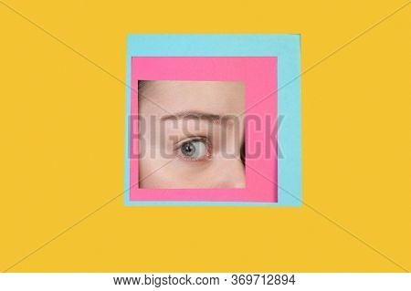 Shocked. Face Of Emotional Caucasian Woman Peeks Throught Square In Yellow Background. Trendy Geomet