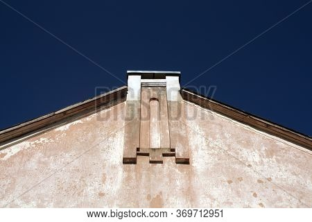 Wall And Roof Of Old House Against Blue Sky. Urban Background