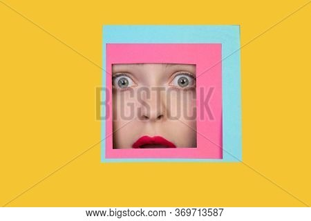 Scared. Face Of Emotional Caucasian Woman Peeks Throught Square In Yellow Background. Trendy Geometr