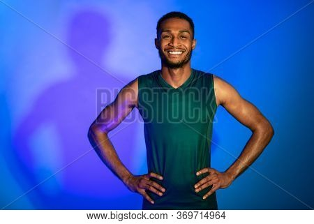 Cheerful Black Athlete Guy In Fitwear Smiling To Camera Posing Over Blue Studio Background. Neon Lig