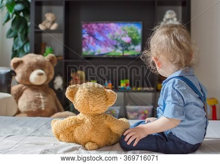 Cute Baby Boy And His Teddy Bear Watching Tv Sitting On A Couch In The Living Room At Home