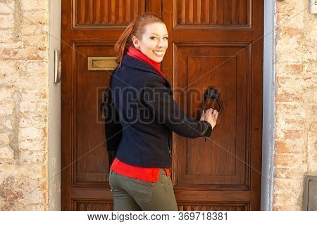 Smiling Traveller Woman In Black Jacket Red Scarf And Green Trousers Is Knocking On An Old Wooden Vi