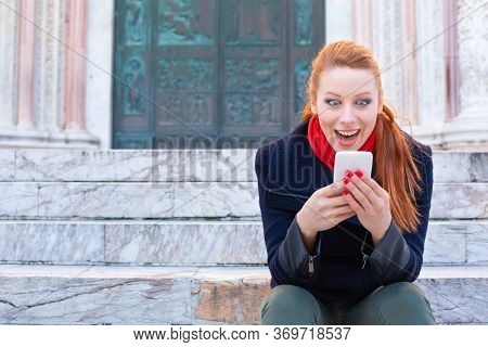 Shocking Sms. Closeup Portrait Funny Shocked Young Girl Looking At Phone Receiving Good News Photos