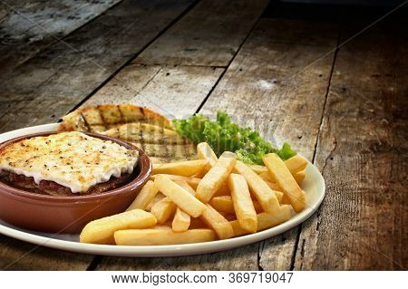 Shot Of A Lasagne Verdi With Chips And Side Salad And Garlic Bread Served In A Plate