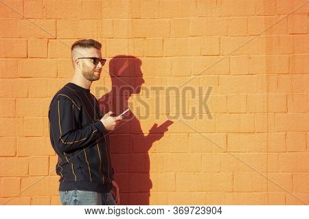 Guy In Casual Wear And Sunglasses With Mobile Phone. Young Caucasian Man With Intense Gaze Standing