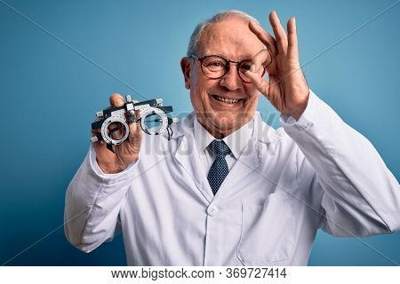 Senior grey haired optic doctor man holding optometrist eyeglasses over blue background with happy face smiling doing ok sign with hand on eye looking through fingers