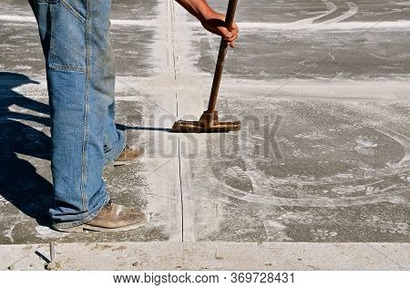 A Construction Worker Cleans Ups Cement Dust After Cutting Expansion Joints On A Newly Poured Garage