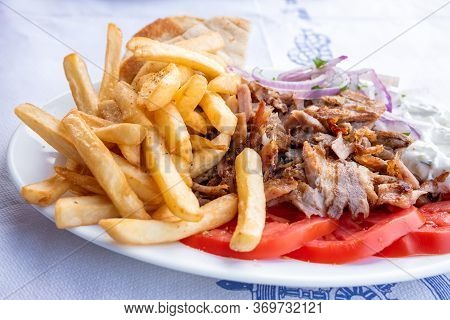 Greek Souvlaki, Traditional Food In Greece, Pork Meat And French Fries With Onion And Tzatziki Sauce