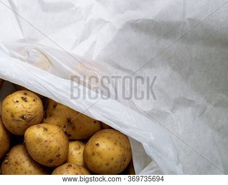 A Pile Of Unwashed Potatoes Lies In A White Bag