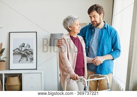 Senior Woman Using Walker And Talking To Her Caregiver He Helping Her During Rehabilitation