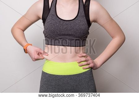 Weight Loss, Slim Body, Healthy Lifestyle Concept. Fit Fitness Girl Measuring Her Waistline. Girl Is