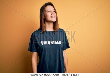 Young beautiful brunette girl doing volunteering wearing t-shirt with volunteer message word looking away to side with smile on face, natural expression. Laughing confident.
