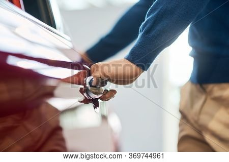 Hand Of Male Unrecognizable Businessman Opening And Holding Red Car Door. Close Up Of Young Caucasia
