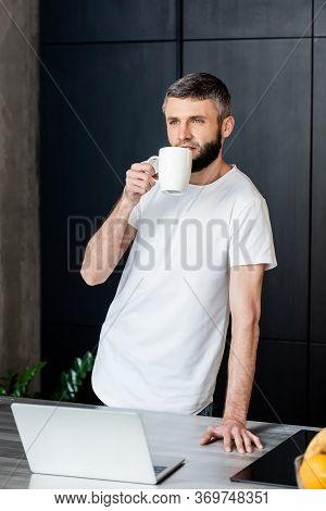 Selective Focus Of Man Holding Mug Near Laptop And Fruits On Kitchen Worktop