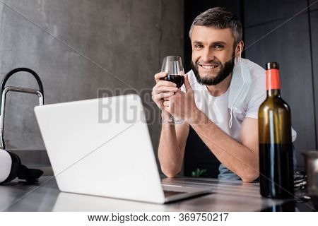 Selective Focus Of Smiling Man In Medical Mask Holding Glass Of Wine Near Laptop And Vr Headset On W