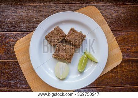 Kibe Roast On White Dish With Lemmon And Onion. Brazilian Snack