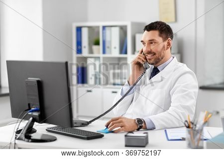 healthcare, medicine and people concept - smiling male doctor with clipboard calling on desk phone at hospital