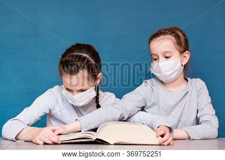 A Girl In A Medical Mask In Quarantine Reads A Book, And Another Girl In A Mask Takes It From Her. E
