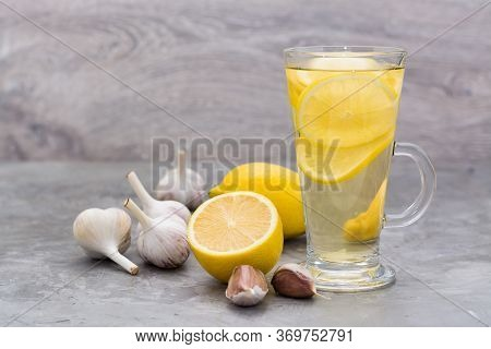 Therapeutic Drink Of Lemon And Garlic In A Glass On The Table. Alternative Medicine