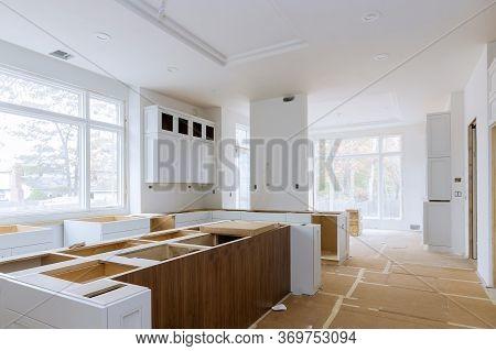 Installation Of Worker Installs To Home Improvement Kitchen Cabinet.