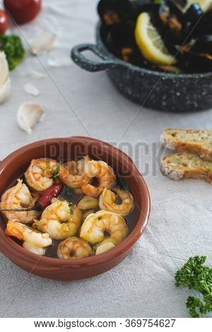 Selective Focus On Traditional Spanish Garlic Prawns Fried In Olive Oil With Parsley