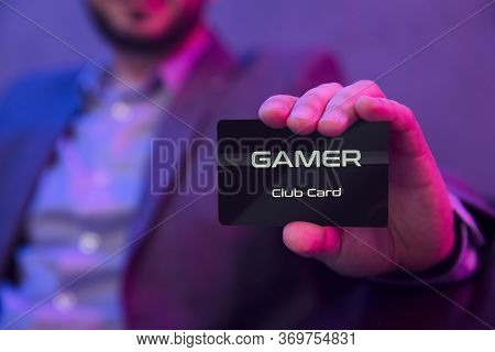 Man's Hand Holds Gamer Clubcard. Gentleman In Suit Holds Gamer Membership Club Card In His Hand
