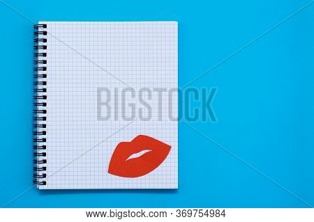 World Kiss Day. Red Lips On A Blank Sheet Of Open Notebook On A Blue Background.