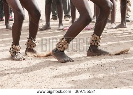 Dance On The Sand. Feet Of Dancing Africans On The Sandy Surface. Four Naked Legs With Traditional O