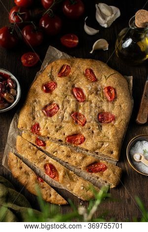 Traditional Italian Homemade Focaccia Bread With Tomatoes, Olive Oil, Rosemary, Olives, Garlic On Ru