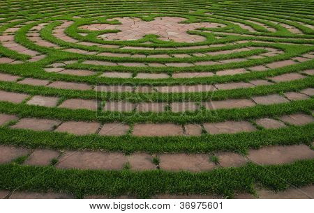 Circular outdoor prayer labyrinth made of bricks and green grass poster