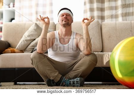 Portrait Of Funny Male Meditating At Home. Middle Aged Man Taking Care Of Body Sitting With Crossed