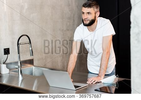 Handsome Man Using Laptop Near Medical Mask On Worktop In Kitchen