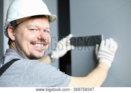 Builder In Helmet Applies Metal Detail To Wall. Quality Work And Selected Design. Builder Takes Into
