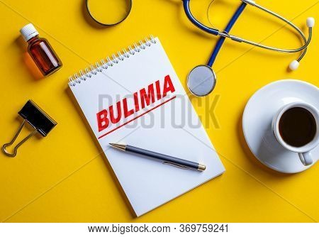 On A Yellow Background Lies A Stethoscope, Pills, Costs Coffee And On A White Sheet The Word Bulimia