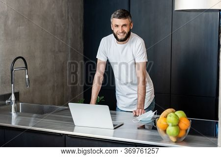 Handsome Freelancer Smiling At Camera Near Laptop And Medical Mask On Kitchen Worktop