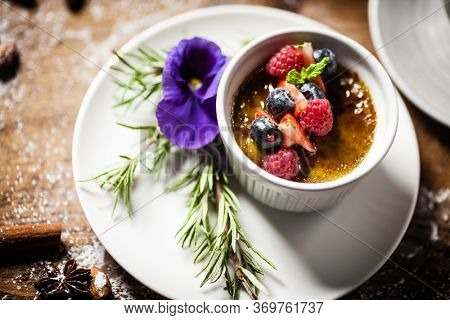 Avocado creme brulee with fresh berries on a plate. Delicious healthy food closeup served for lunch on a table in modern gourmet cuisine restaurant.