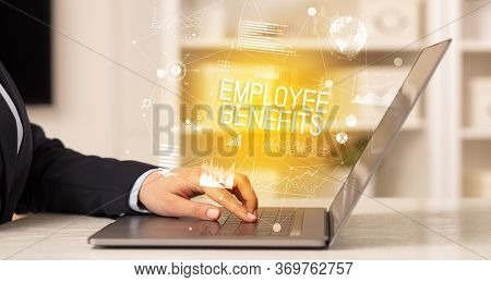 Side view of a business person working on laptop with EMPLOYEE BENEFITS inscription, modern business concept